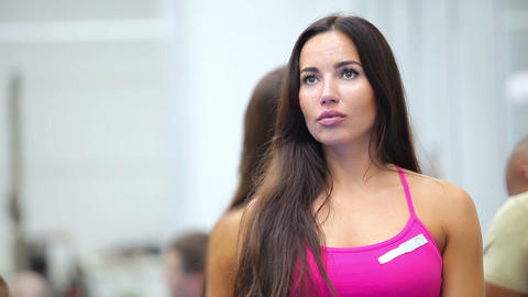 Beautiful young woman listening a coach on the training in the gym Live Action