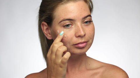 Beautiful woman with freckles, applies cream touching and checking her skin, Live Action