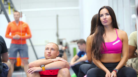 Beautiful woman and young man listening a coach on the training in the gym Live Action