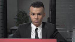 Young successful African businessman sitting in office, working on a laptop Footage