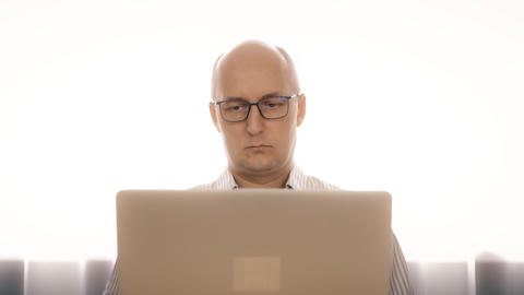 Sadness man in glasses working on notebook and rubbing eyes from fatigue Footage