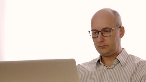 Surprised bald businessman in glasses looking at laptop screen with astonishment Footage