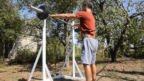 man takes a bar to perform squats. Exercises in bodybuilding. sport in the Archivo