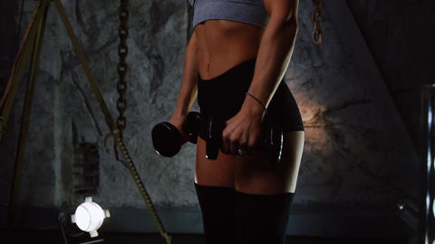Sporty girl in sexy clothes doing exercises on the shoulders with dumbbells Footage