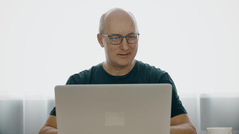 Portrait of a man in glasses, working behind laptop and smiling happily. The man Footage