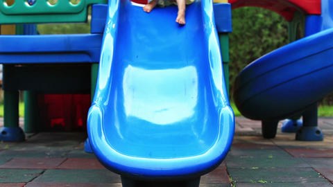 Cute little girl, outside in summer, playing on a slide Stock Video Footage