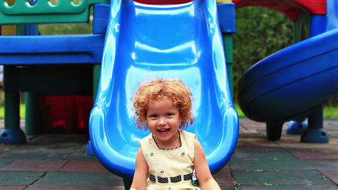 Cute little girl, outside in summer, playing on a slide Footage