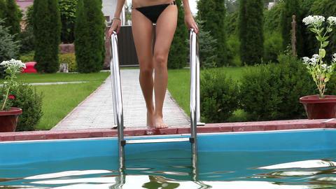Pretty girl in bikini stepping down swimming pool stairs Stock Video Footage