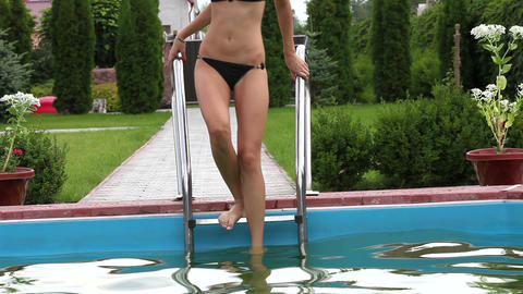 Pretty girl in bikini stepping down swimming pool stairs Stock Video Footage