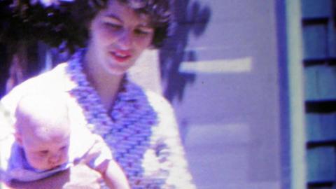 1963: Jackie ONassis look alike style mother carries baby Footage