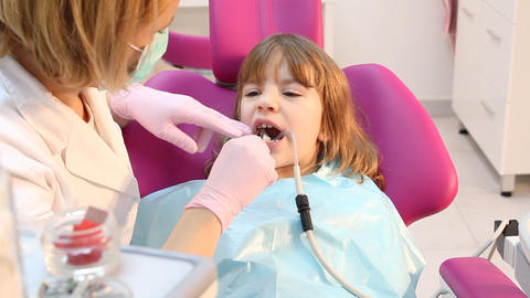 beautiful little girl with open mouth during drilling treatment at the dentist ビデオ