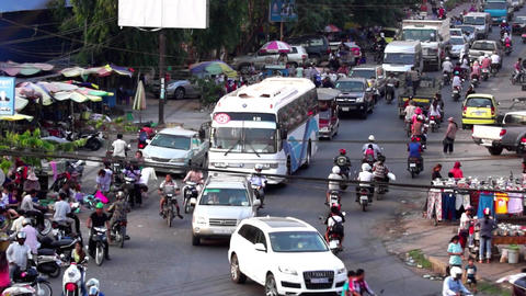 Vehicles and people in rush hour at a busy intersection in a typical S.E. Asian  Footage