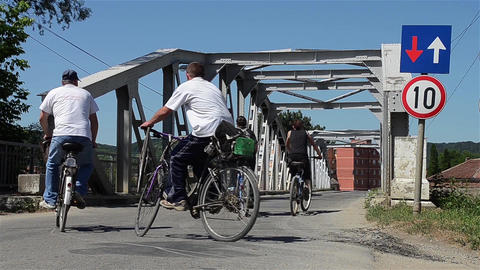 Cyclists and cars passing over an old metal bridge 21 Footage