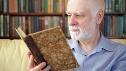 Elderly senior man relaxing at home reading book enjoying retirement Footage