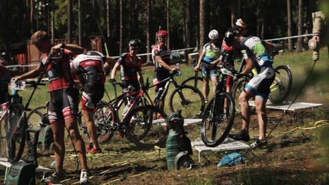 Sportsmen group washing bicycles with compressor outdoors Live Action