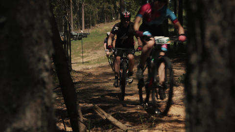 Bicyclists racing in woods behind trees on dusty road Footage