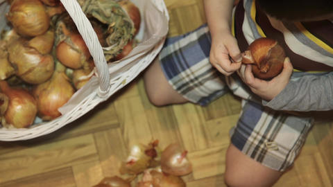 Little boy cleans onions sitting on the floor in the kitchen Live Action