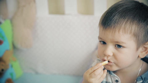 The little boy sits on the bed and eats delicious sweet sticks Footage