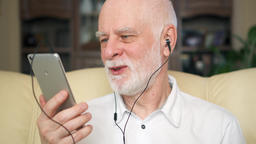 Modern senior man listening music with earphones on smartphone. Pensioner Footage