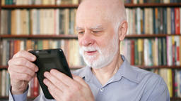 Elderly senior man relaxing at home reading e-book enjoying retirement Footage
