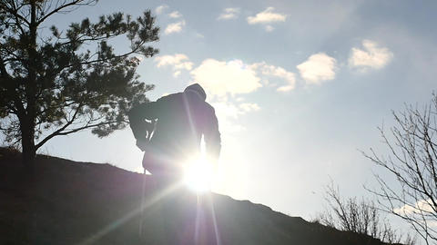 silhouette of disabled man on crutches climbing up to mountain Archivo