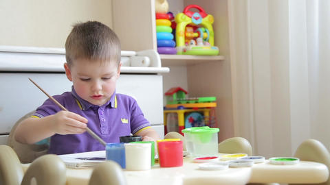 The child in kindergarten paints with a brush with colored paints Footage