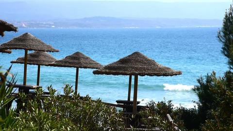 Straw parasols by the sea in Le Bombarde beach, Alghero. Sardinia, Italy Footage