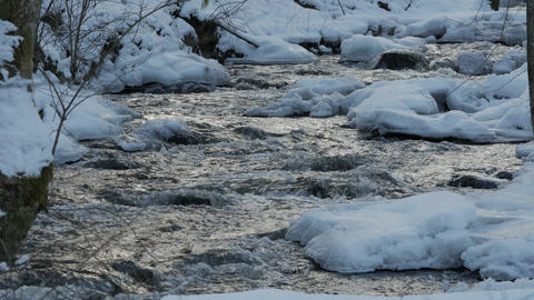 A beautiful crystal clear stream in winter with snow flows through woods Footage
