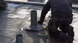 Moers / Germany - February 01 2018 : Roofer installing chimney using bitumen and Footage