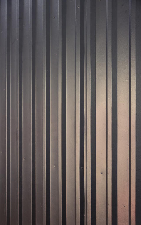 Steel corrugated sheet painted black, interior shot with some reflecting lights Photo