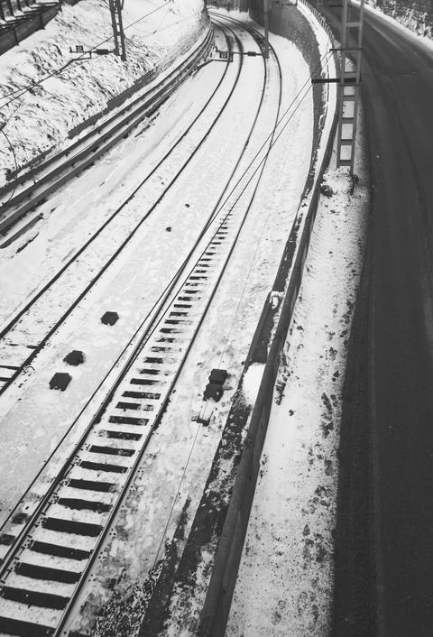 Black and white photo of winter rail track with road running along フォト