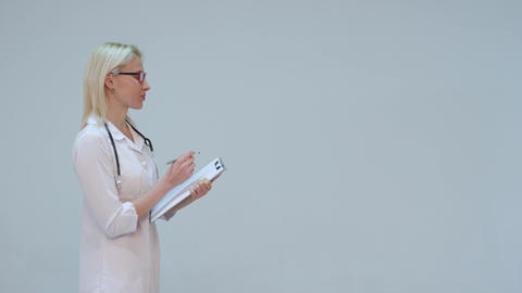 Blond Doctor writing on a clipboard while smiling against a grey background Live Action