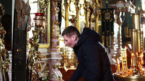 The young man bows and kisses the cross in the Orthodox Church Footage