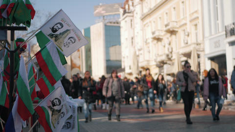 Bulgarian flags waving in downtown with people walking by Archivo