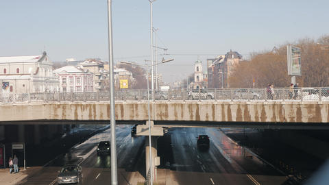 Bridge over boulevard - urban scene cityscape with cars and pedestrians Footage