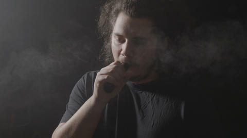 Nonconformist young man with long hair vaping and blowing huge clouds of steam Footage