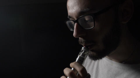 Sad depressed young IT engineer boy with glasses performing vaping tricks in a Live Action