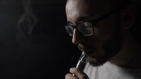 Smoking addicted young man with glasses vaping electronic cigarette exhaling Footage