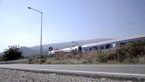 High speed train passing along a paved road on that walk a woman 54 Footage