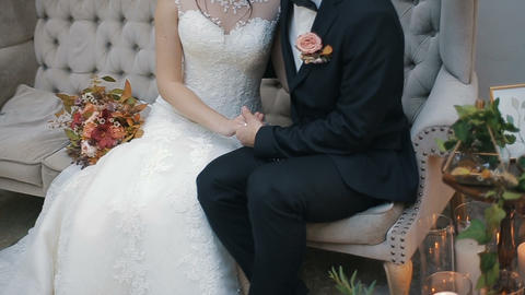 Wedding couple holding hands, happy groom and bride indoor sitting on a couch Footage
