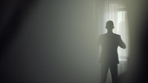Young man wears a suit in front of the window Footage