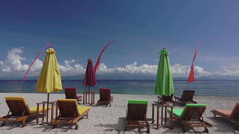 Empty Sunbeds and Umbrellas on the Beach. Slow Motion Footage