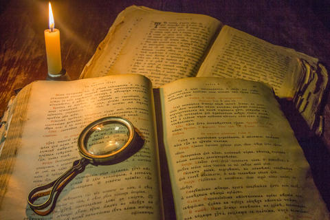 An open ancient prayer books and a magnifying glass on its open pages under the Fotografía