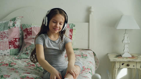 Smiling cute little girl in headphones dancing and moving her head funny while Footage