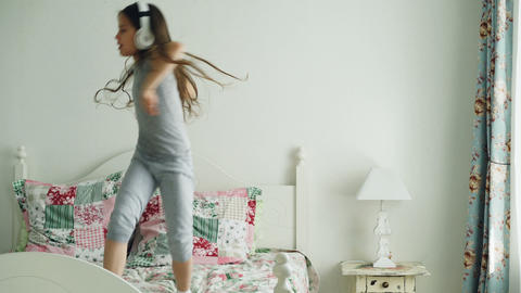 Funny cute little girl in wireless headphones dancing and have fun on bed at Footage