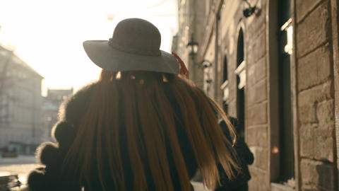 Young woman with beautiful long hair walking the city street, turns to camera Footage