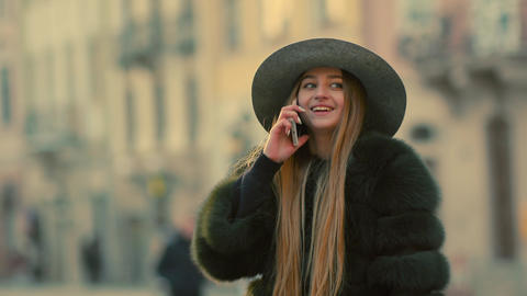 Young woman in a bright sunlight uses her phone smile talks in the phone Footage