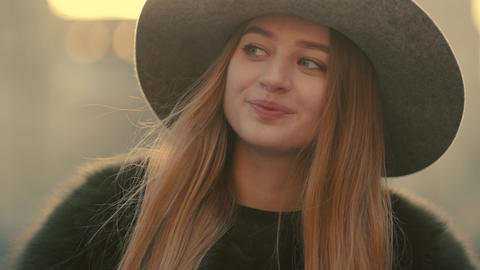 Glamorous young woman in a gray hat charmingly looks right and smile towards the Footage