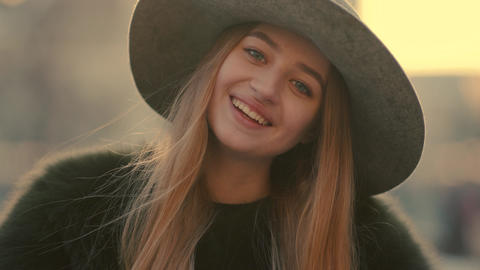 Glamorous young woman in a gray hat charmingly looks right and smile towards the Live Action