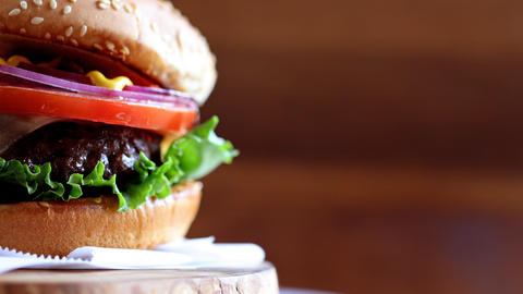 Close-up of burger with copyspace rotating on wooden texture Archivo